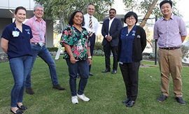 Four male and three female members of the Fiona Stanley Hospital renal team stand in a garden