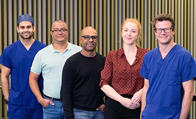 A team of four male and one female researchers stand against a ballustrade