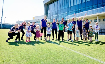 Ten young children and a number of male and female Fremantle Dockers players and staff stand on a footballe oval