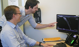 Two men review an x-ray image on a computer screen