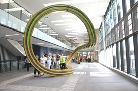 Visitors take a guided tour inside Fiona Stanley Hospital, stop to look at the art sculpture bench in the main concourse