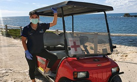 A young women leans against an offroad buggy on a beach. She wears a surgical mask and gloves.
