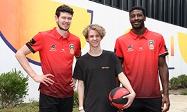 Two mean wearing Perth Wildcats team shirts stand with a teenage boy who holds a basketball.