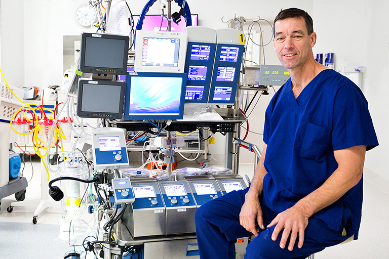 A man in blue hospital scrubs seated in front of medical equipment