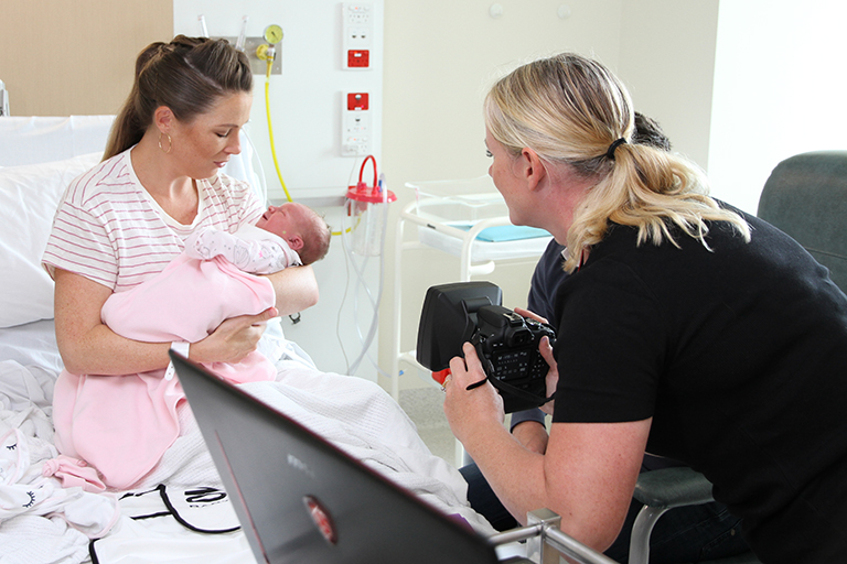 A woman photographs another woman who is holding a newborn baby.