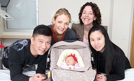 A young man and woman are beside a newborn baby in a capsule that is resting on a hospital bed. A female nurse and another woman stand with them.