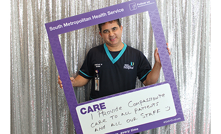 A male nurse holds a sign that reads 'Care – I provide compassionate care to all our patients and all our staff.'