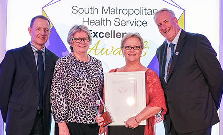 Two men and two women stand in front of a banner that reads South Metropolitan Health Service Awards. One of the women holds a certificate and an award trophy.