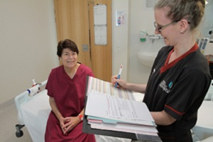 A woman in pyjamas sitting on a bed while a nurse holding a clipboard stands beside her