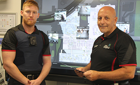 Two men stand in front of a large wall mounted screen which shows a map of a hospital campus.