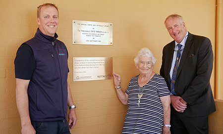 Two men and a woman stand in front of a wall with two plaques attached. The woman's had is on a plaque that reads 'In reocgnition of the commitment and dedication shown to those in need by Registered Nurse Fay Sullivan at the Rottnest Island Nursing Post and after who Fay's Bay is named'