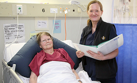 A nurse stands beside a female patient in a hospital bed