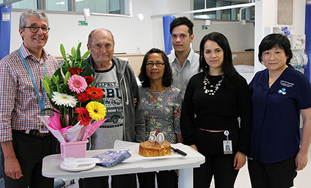 Six people standing in a treatment area. In front of them on a table is some flowers and a cake.