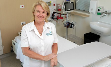 Lynda Deacon standing by a hospital bed
