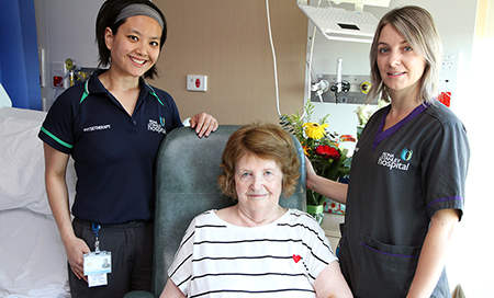 A young female physiotherapist and a young female nurse stand beside and older woman seated in a chair.