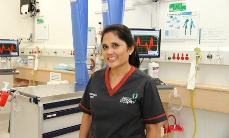 Registered nurse Aida Oakdon standing amongst medical equipment