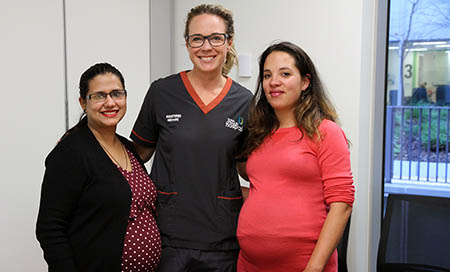 A female registered midwife stands between two pregnant women