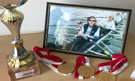 A photo of a woman rowing with four medals and a trophy in front of it