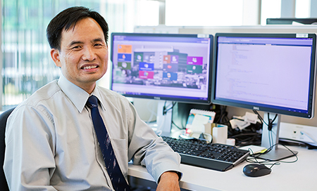 A smiling man sits in front of a computer at a desk.