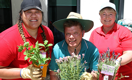 A man standing between two women and all are holding pot plants