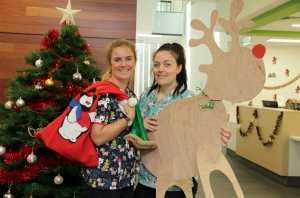 Two female Radiation Oncology staff holding a Santa sack and a cardboard reindeer