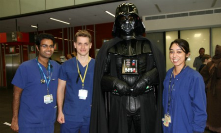 Three staff members wearing scrubs alongside person in Darth Vader costume
