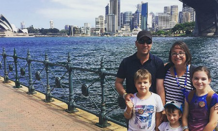 Family of five stands in front of Sydney city landscape