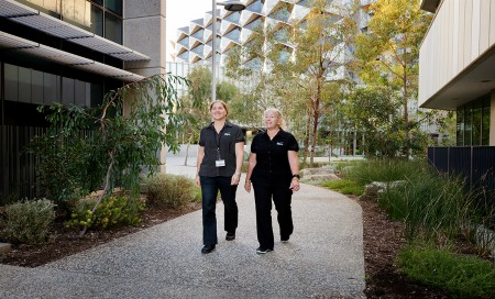 Two staff members walking through hospital grounds