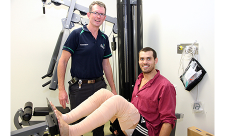 A male physiotherapist stands beside a young man on a piece of fitness equipment