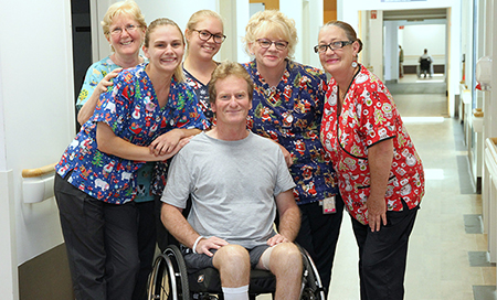 A young man sits in a wheelchair with five female nurses standing beside him. The nurses all wear bright surgical scrubs featuring Christmas designs.