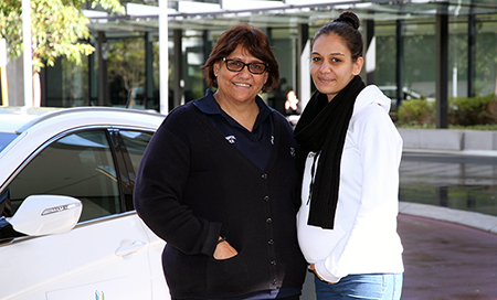 Two Aboriginal women standing beside a Fiona Stanley Hospital car