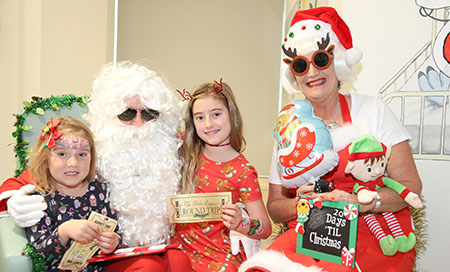 Two young girls with their faces painted stand next to Santa and Mrs Claus