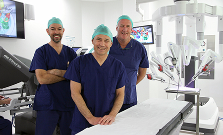 Three men in surgical scrubs standing in an operating theatre