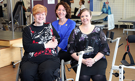 Three women are seated in a gym therapy area. One of the women is seated in a wheelchair.