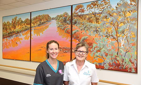 Two female nurses stand in front of a large, colourful artwork
